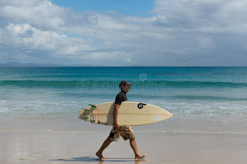 Le surfer marche dans la plage de Byron Bay photos stock