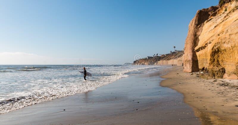 Le surfer masculin solitaire entre dans l'océan chez Solana Beach images stock
