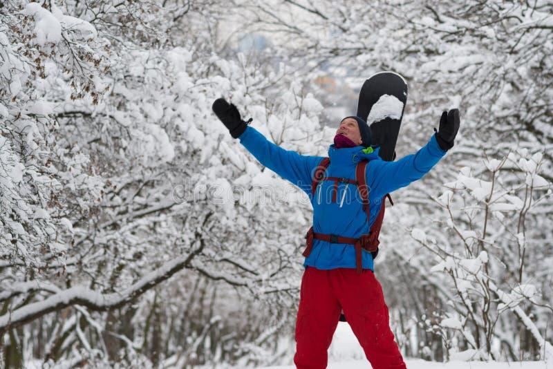 Le surfeur, avec les bras ouverts, est enchanté dans la forêt d'hiver image libre de droits