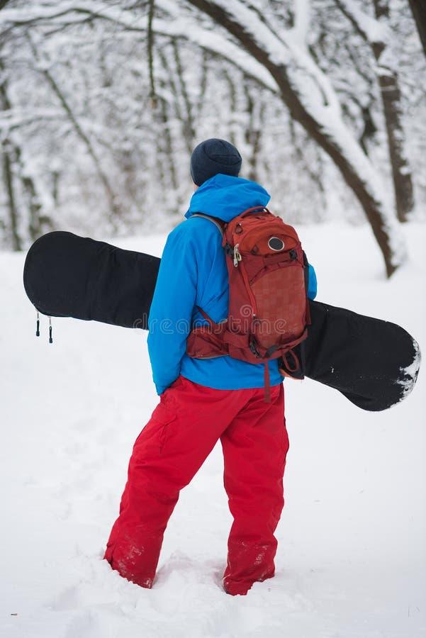 Le surfeur avec le sac à dos se tient dans la forêt après des chutes de neige photographie stock