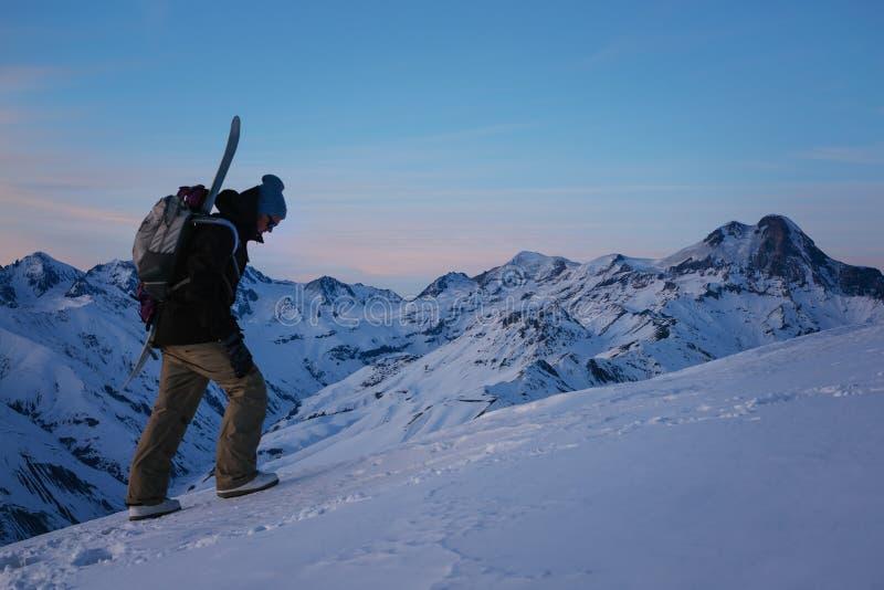 Le surfeur courageux avec le sac à dos et le surf des neiges s'élèvent à la montagne neigeuse à la soirée images libres de droits