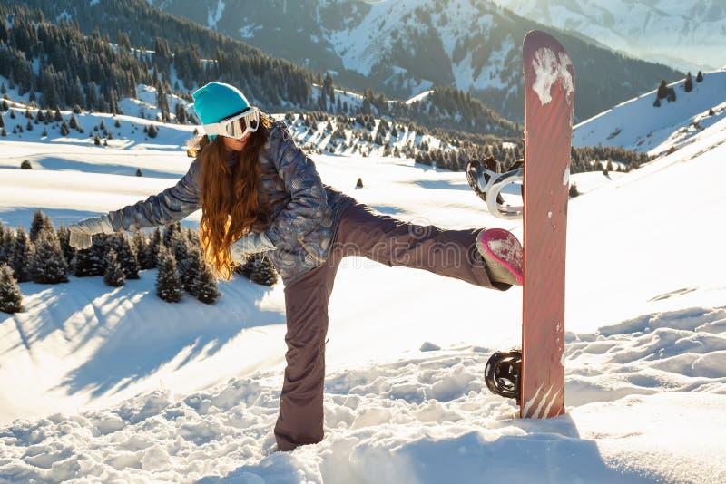 Le surfeur de fille tient le dessus de montagne avec le surf des neiges dans des mains images stock