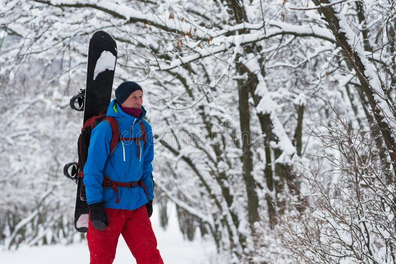 Le surfeur de sourire avec le sac à dos marche par la forêt images libres de droits