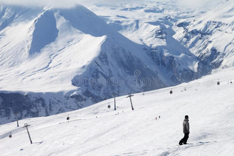 Le surfeur descendent sur la pente de ski et l'ascenseur neigeux de gondole photos stock