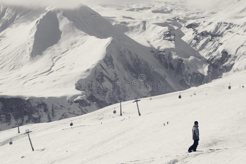 Le surfeur descendent sur la pente de ski et l'ascenseur neigeux de gondole photographie stock