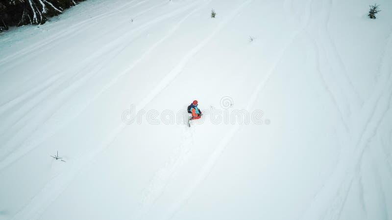 Le surfeur s'assied dans la neige et dispose à descendre images stock
