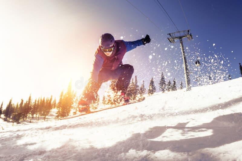 Le surfeur saute la lumière du soleil de pente de ski photo libre de droits