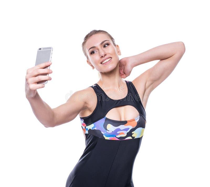 Le survêtement de port de vêtements de sport de jeune femme heureuse de forme physique prend le selfie avec son téléphone portabl images libres de droits