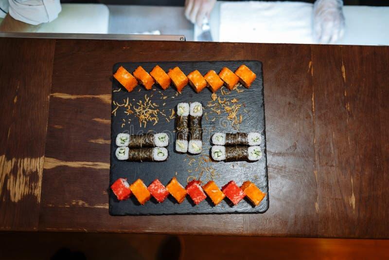 Le sushi roule l'ensemble sur le conseil noir sur la table en bois images stock