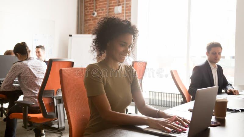 Le svart kvinnlig anställd som arbetar på bärbara datorn i delat kontor fotografering för bildbyråer