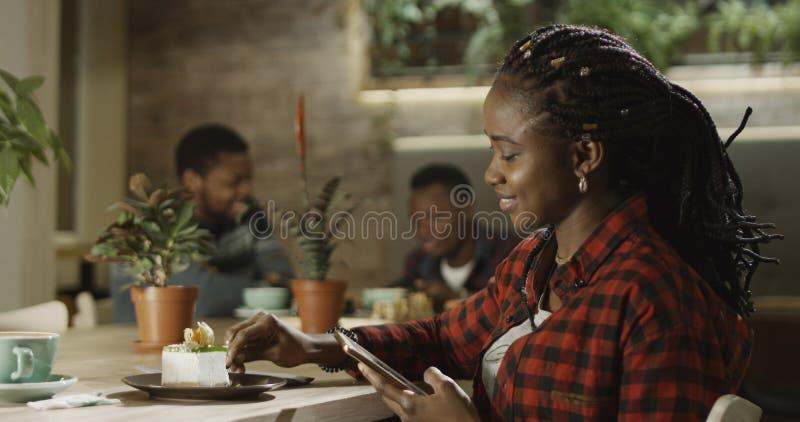 Le svarta kvinnan med telefonen i kafé arkivbild