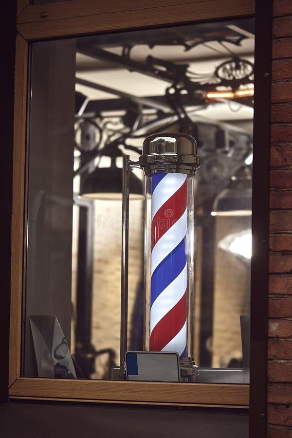 Le symbole célèbre d'un salon de coiffure avec lui rayures rouges, bleues et blanches de tourbillonnement photos stock