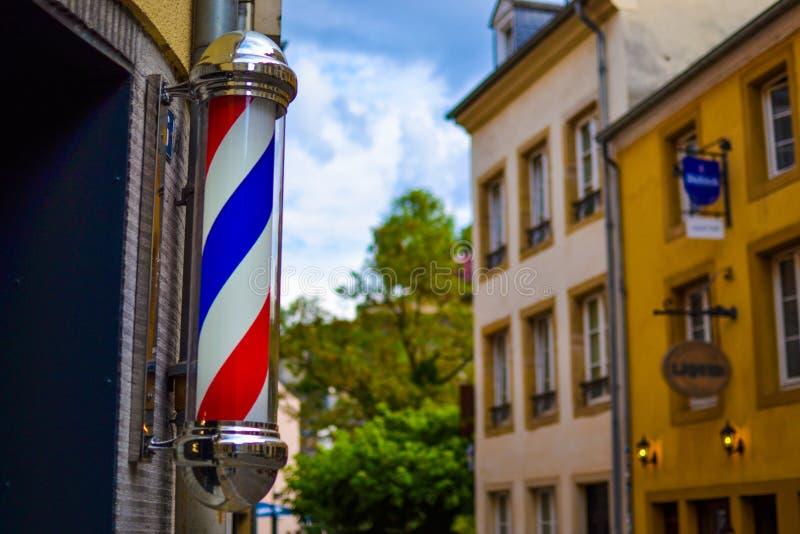 Le symbole célèbre et classique d'un salon de coiffure Fermez-vous de la lumière rouge, blanche et bleue de rotation de salon de  images libres de droits