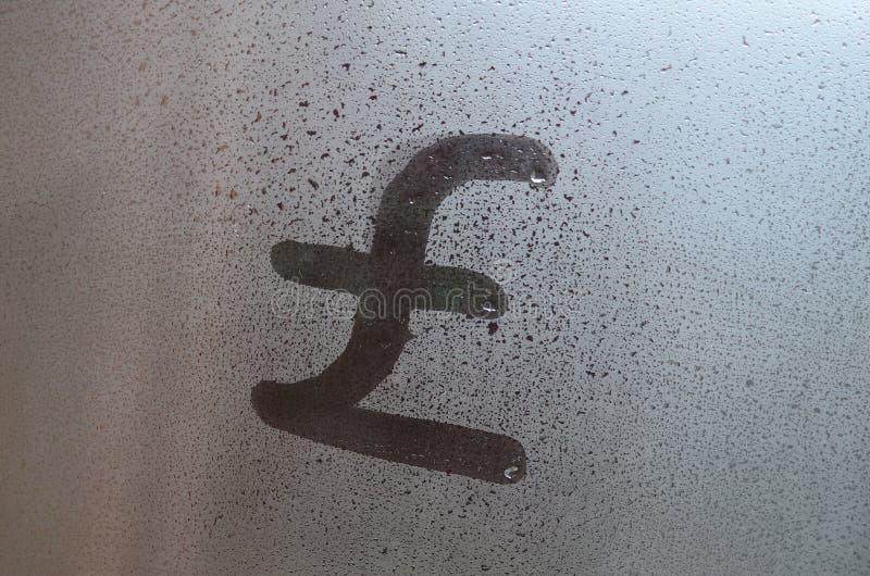 Le symbole de livres anglaises est écrit avec un doigt sur la surface du verre misted photos stock