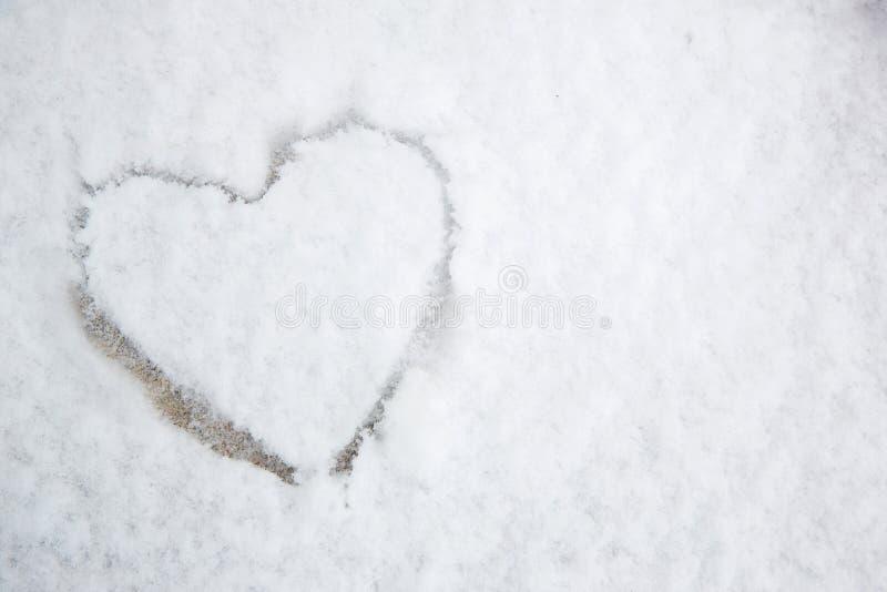Le symbole du coeur, peint sur la neige blanche fraîche images libres de droits