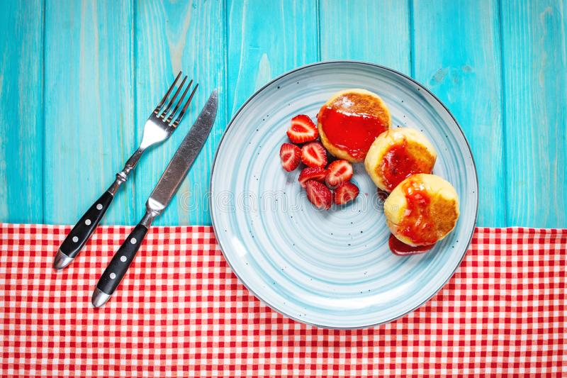 Le syrniki russe ou les beignets ou les crêpes de fromage blanc ont servi avec la fraise sur le fond en bois bleu image stock