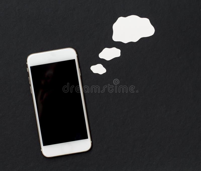 Le téléphone blanc avec le blanc bouillonnent cependant sur le fond noir photos libres de droits