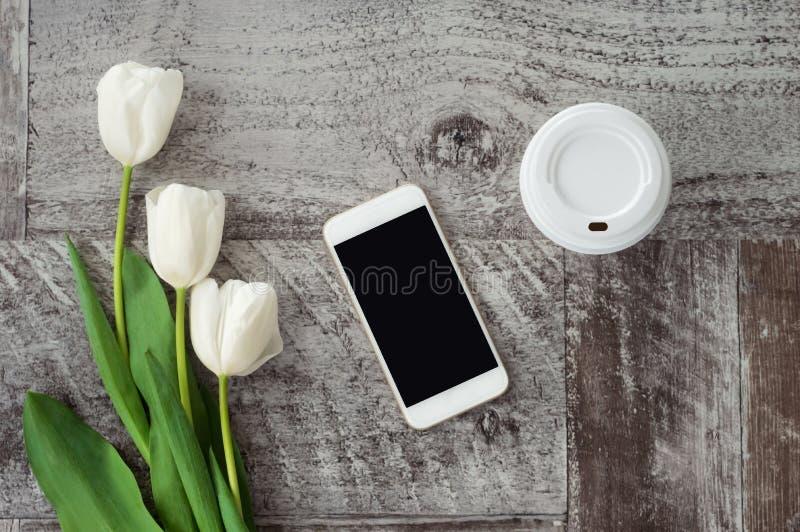 Le téléphone, le café et les fleurs blancs sont sur la table Travail ? la maison ind?pendant photos stock
