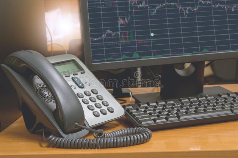 Le téléphone d'IP avec le clavier d'ordinateur et le moniteur montrent le diagramme financier sur l'écran image stock