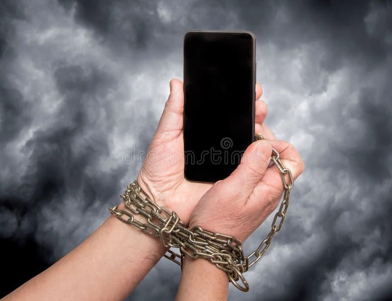 Le téléphone est enchaîné aux mains sur le ciel dramatique foncé de fond La dépendance à l'égard le phone_ mobile photographie stock