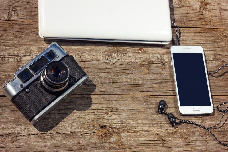 Le téléphone et l'ordinateur portable d'appareil-photo sont sur une table en bois photos libres de droits