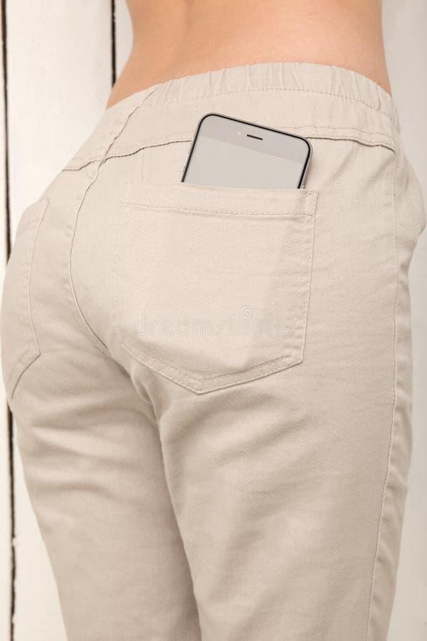 Le téléphone intelligent dans une poche halète, belle fille avec le butin sexy images stock