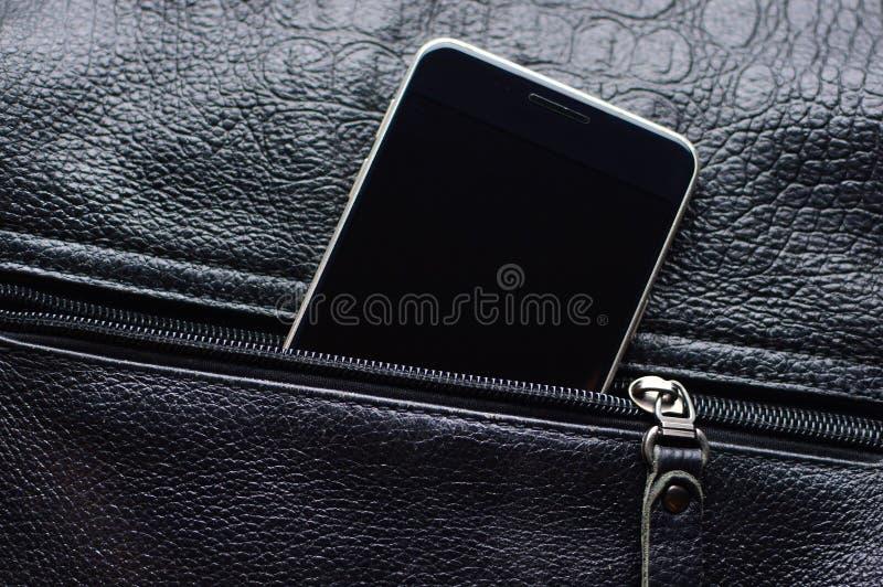 Le téléphone intelligent noir regarde de la poche en cuir défaite la fermeture éclair image stock