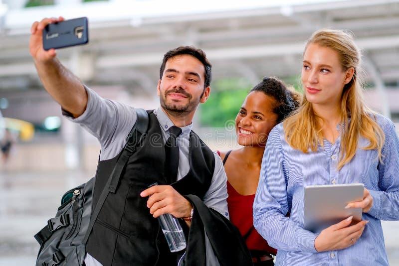 Le téléphone portable blanc d'utilisation d'homme d'affaires au selfie avec les femmes de métis et blanches et tous semblent heur image libre de droits