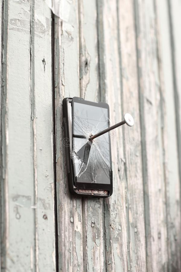 Le téléphone portable défectueux est cloué à une vieille barrière photographie stock libre de droits