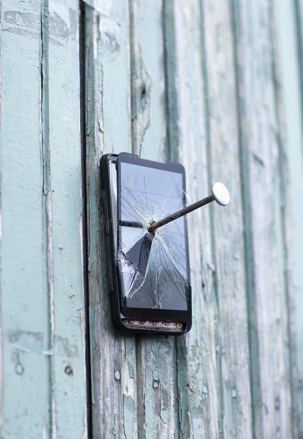 Le téléphone portable défectueux est cloué à une vieille barrière images stock