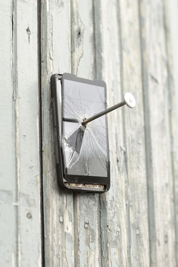 Le téléphone portable défectueux est cloué à une vieille barrière image stock