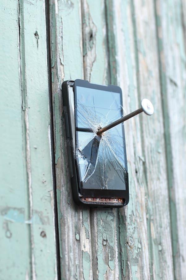 Le téléphone portable défectueux est cloué à une vieille barrière photos stock