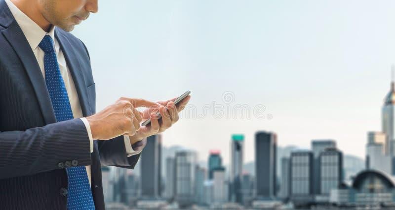 Le téléphone portable d'utilisation d'homme d'affaires au sommet de l'immeuble de bureaux voient la vue images stock