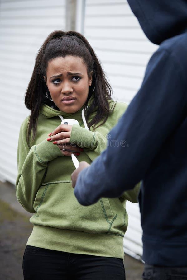 Le téléphone portable de Stealing Teenage Girl de voleur photo libre de droits