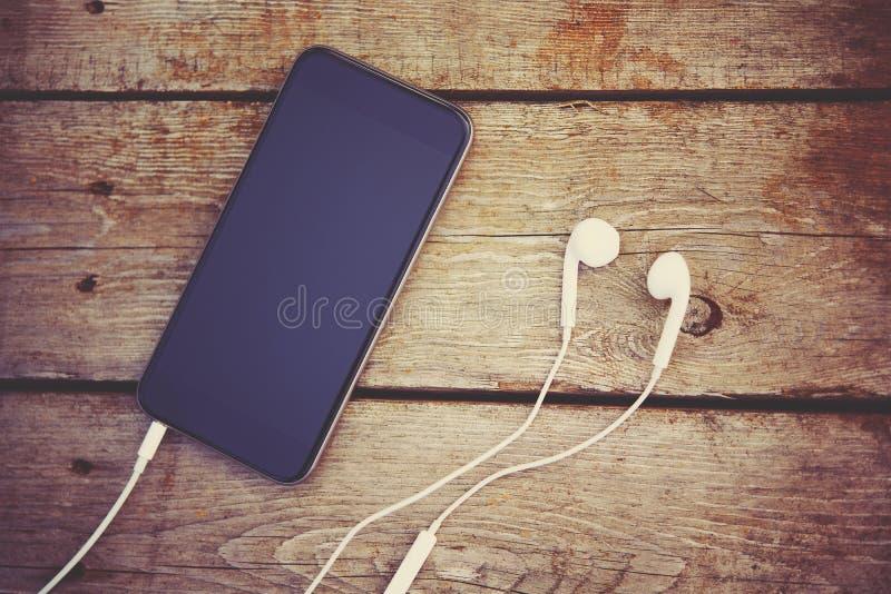 Le téléphone portable et les écouteurs s'étendent sur la vieille table en bois photos stock