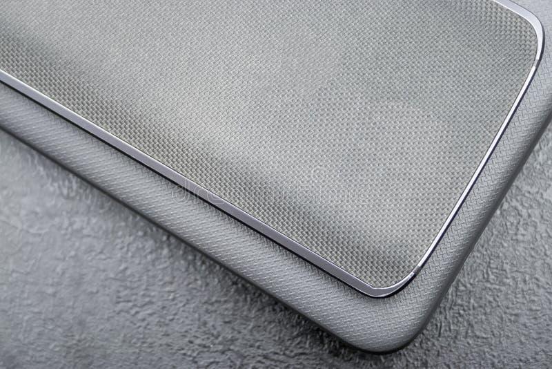 Le téléphone portable gris avec un dos en nylon tricoté se trouve sur une couverture texturisée fermée d'ordinateur portable sur  image stock