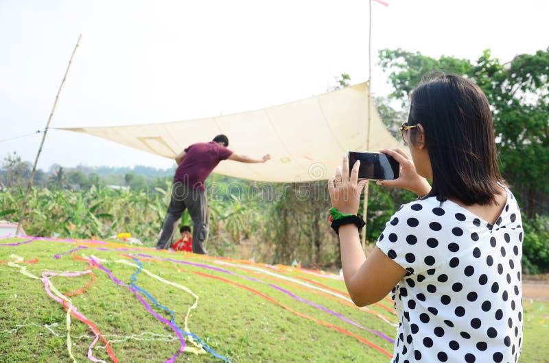 Le téléphone portable thaïlandais d'utilisation de femmes prennent la cérémonie de photo images stock