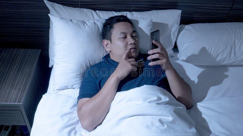 Le téléphone s'est adonné, homme utilisant le téléphone intelligent sur le lit à minuit image stock