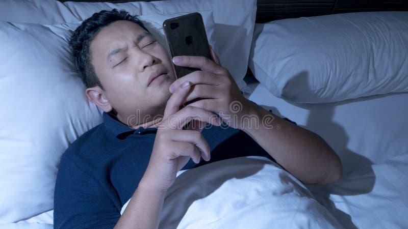 Le téléphone s'est adonné, homme utilisant le téléphone intelligent sur le lit à minuit images stock