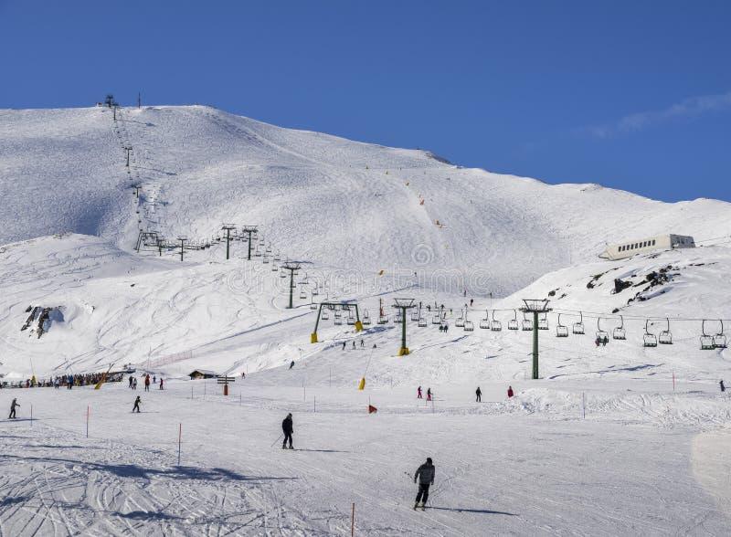 Le télésiège au secteur italien de ski sur la neige a couvert des Alpes et des skieurs et des surfeurs sur la piste - concept de  photographie stock libre de droits