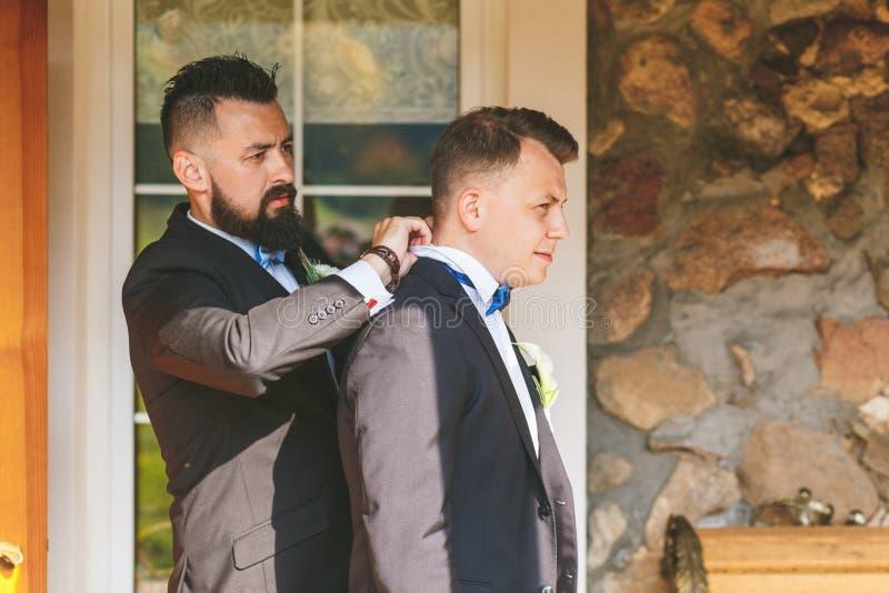 Le témoin aide la jeune mariée à utiliser une veste photographie stock