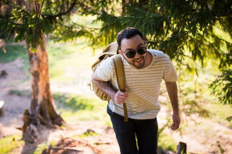 Le T-shirt blanc de port et les lunettes de soleil de jeune homme élégant beau avec le sac à dos dans sa main voyage dans les boi image libre de droits