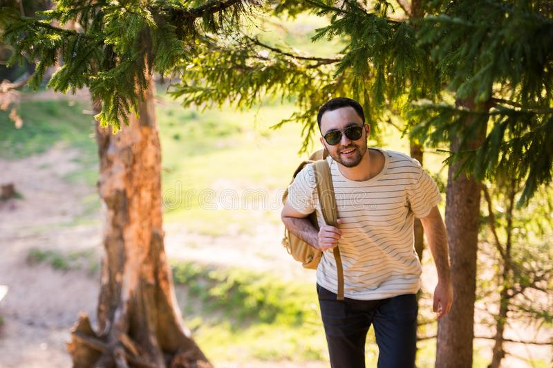 Le T-shirt blanc de port et les lunettes de soleil de jeune homme élégant beau avec le sac à dos dans sa main voyage dans les boi photographie stock libre de droits