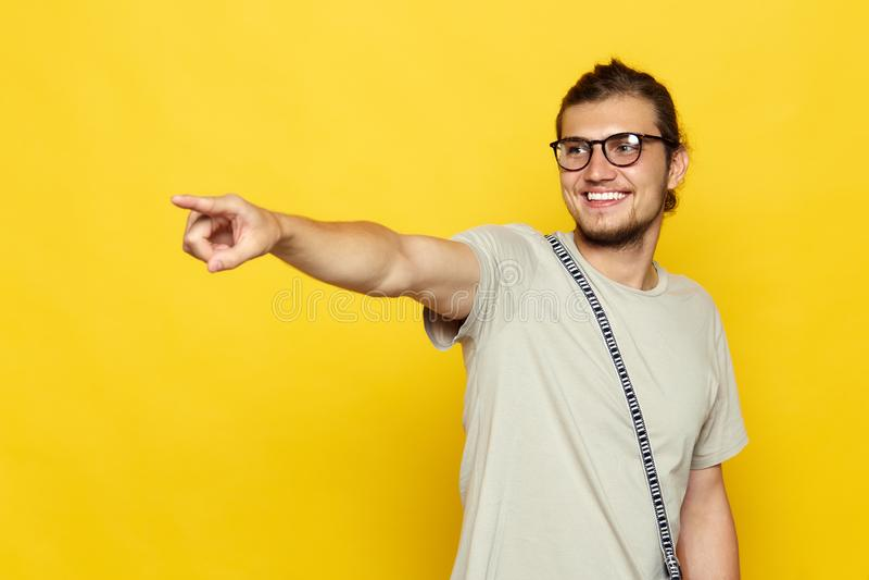 Le T-shirt d'homme non rasé élégant portant des points à l'espace de copie sur le mur jaune montre aussi quelque chose agréable,  photographie stock libre de droits