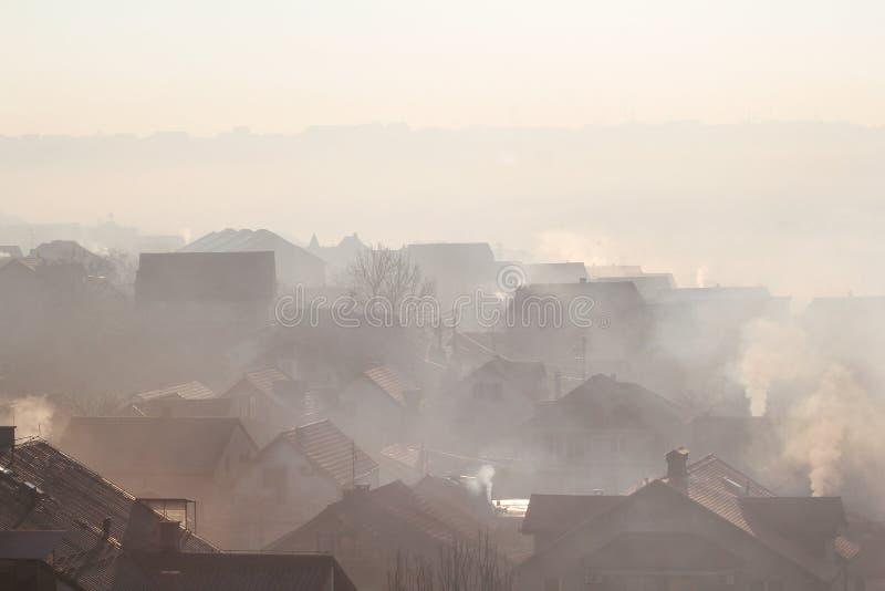 Le tabagisme des cheminées aux toits des maisons émet la fumée, brouillard enfumé au lever de soleil, polluants écrit l'atmosphèr images libres de droits