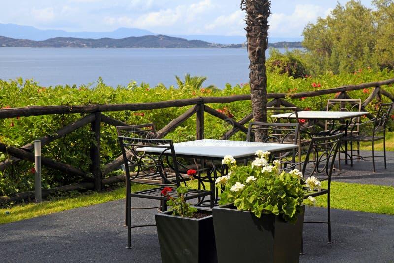 Le Tabelle e le sedie del ferro sul terrazzo con il mare osservano (la Grecia) fotografie stock