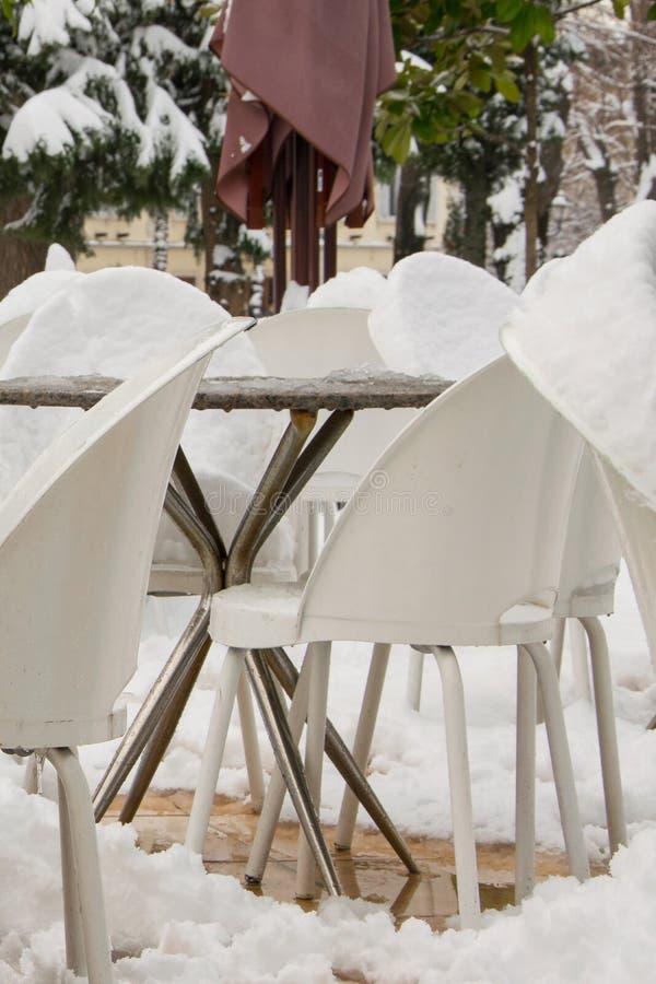 Le Tabelle e le sedie di un caffè escludono, coperto di neve fotografie stock