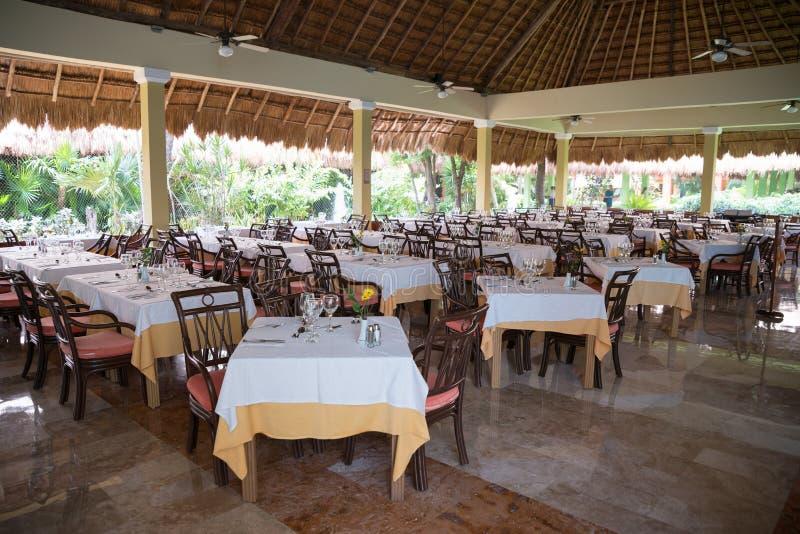 Le Tabelle hanno messo in un ristorante ad un hotel tropicale sotto foglia di palma r fotografia stock