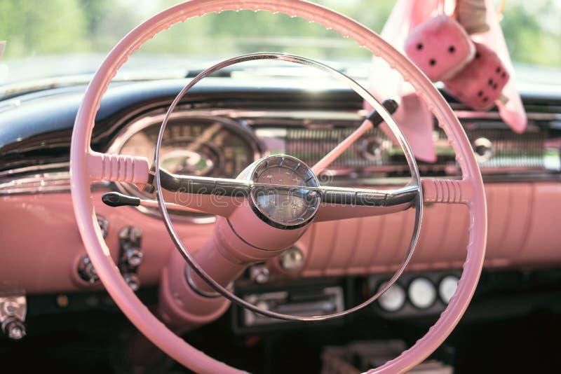 Le tableau de bord et le volant roses d'une voiture classique image libre de droits