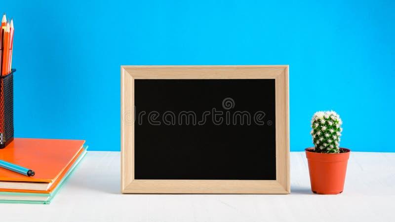 Le tableau noir avec la moquerie vers le haut du cadre et le livre crayonnent sur la table en bois photos libres de droits
